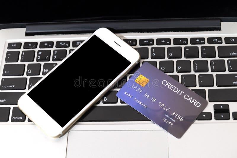 在手机旁边把放的信用卡在膝上型计算机键盘上 免版税库存照片