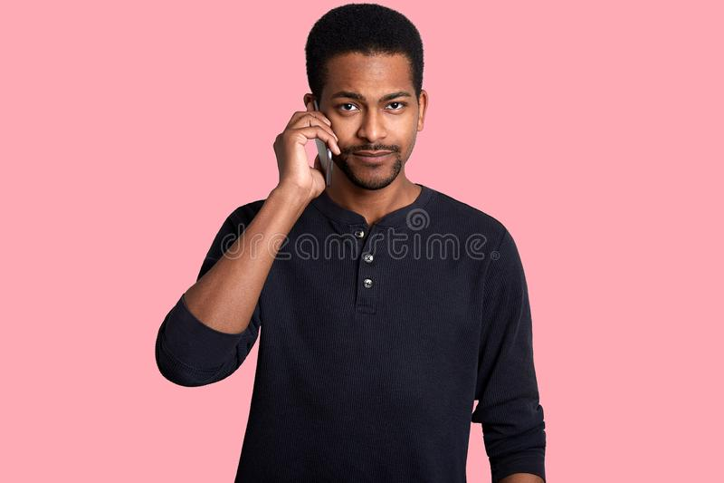 在手机的黑人谈话,discuses重要题目 有哀伤的表示的英俊的非洲人,看照相机,摆在  免版税库存图片