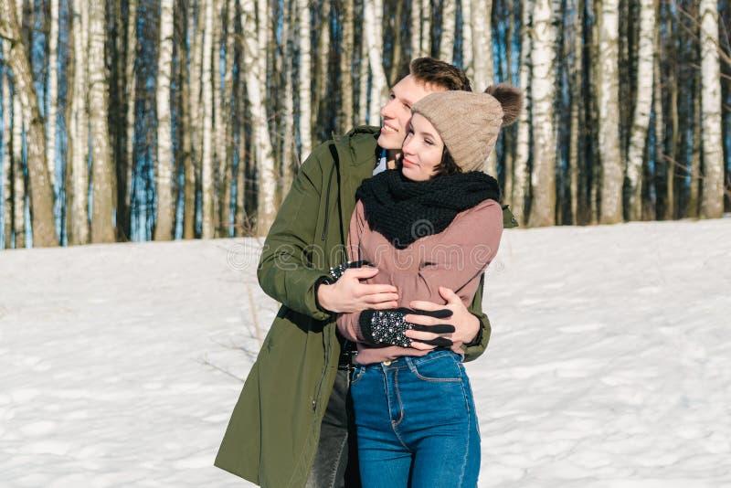 在拥抱在公园的爱的美好的年轻夫妇在一个清楚的晴朗的冬日 年轻人和女孩调查距离 库存照片