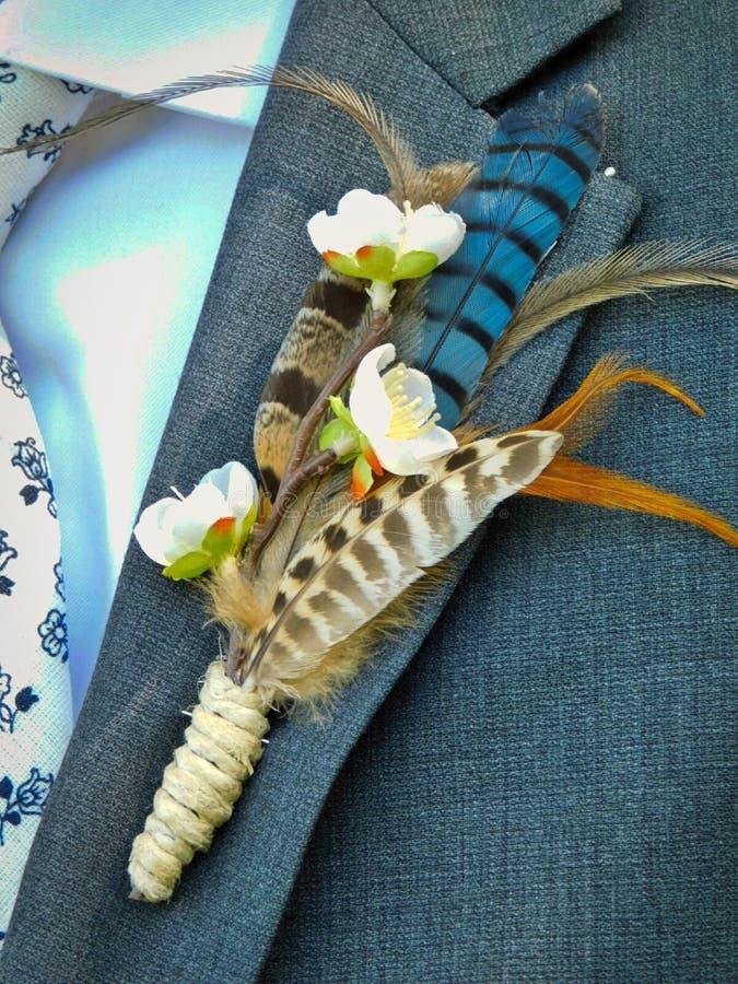 在新郎的翻领的一朵独特的羽毛钮扣眼上插的花 免版税库存照片