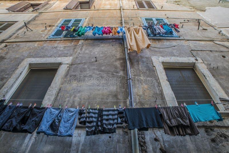 在洗衣店线的垂悬的洗衣店在窗口前面在意大利 免版税库存图片