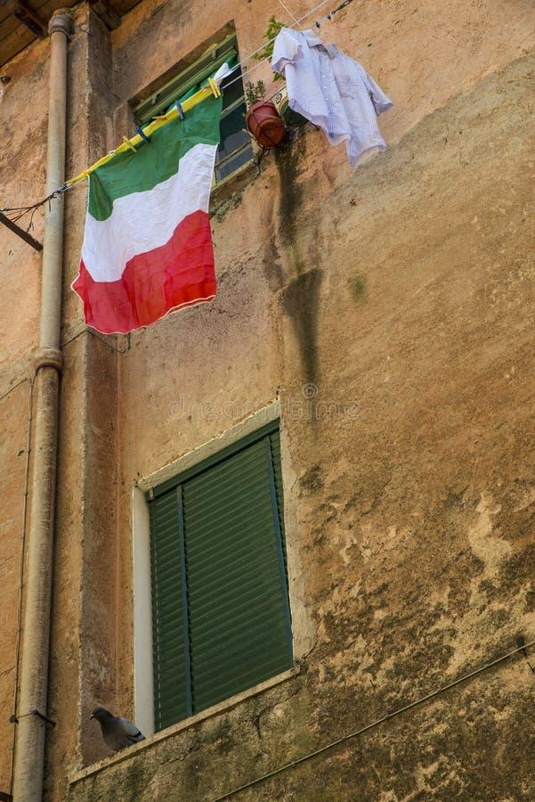 在洗衣店线的垂悬的洗衣店在窗口前面在意大利 库存图片