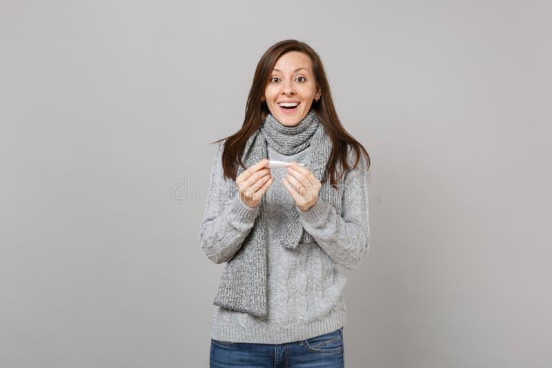 在灰色墙壁背景隔绝的灰色毛线衣围巾藏品温度计的快乐的激动的年轻女人在演播室 健康 免版税库存照片