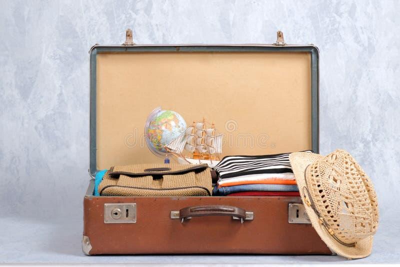 在灰色背景的充分的旅行手提箱,打开了与旅行衣物,辅助部件的案件 与拷贝空间的横幅大模型 旅行或t 免版税库存照片