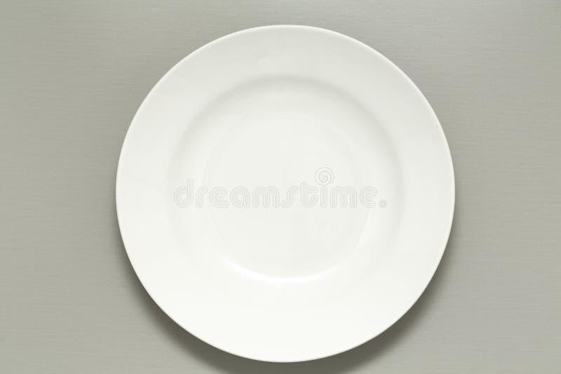 在灰色背景的空的白色陶瓷板材 顶视图 免版税库存照片
