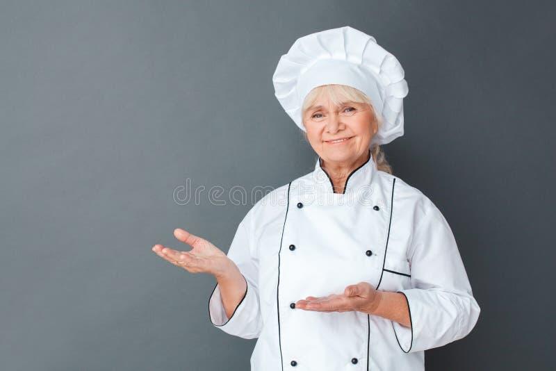 在灰色隔绝的资深妇女厨师演播室身分指向在旁边欢迎看的照相机愉快的特写镜头 免版税库存图片