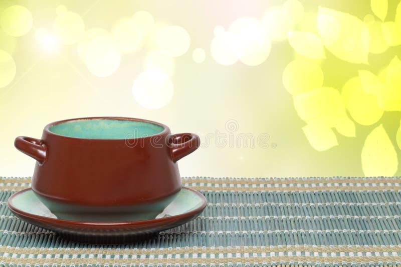 在碗背景的台式 在板材的空的棕色陶瓷汤碗在抽象明亮的黄色的一张绿色竹秸杆席子 免版税库存图片
