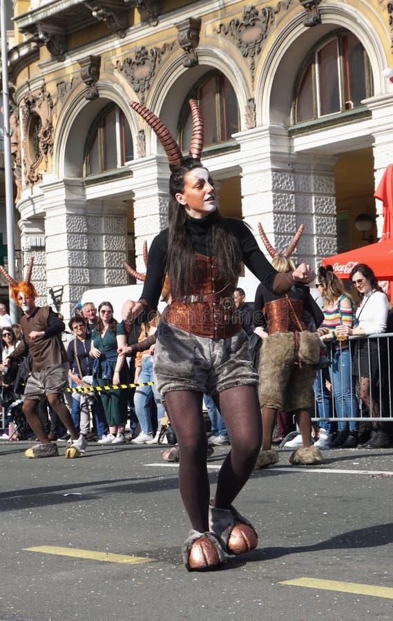 在神平底锅掩没的街道上的女孩跳舞在狂欢节庆祝天 库存图片