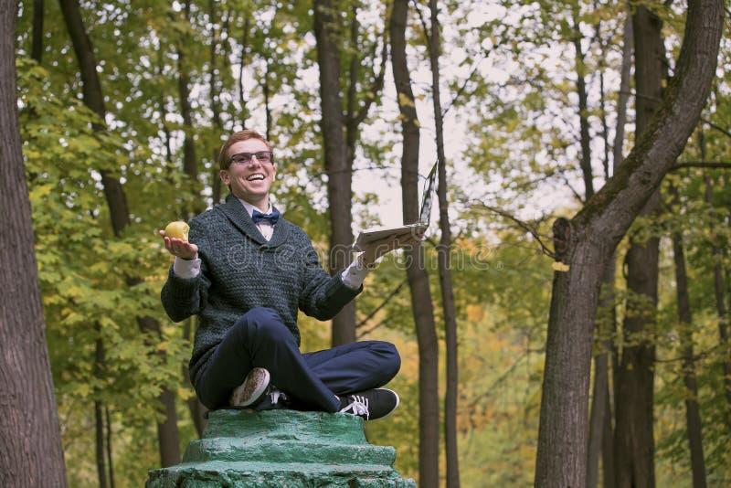 在秋天公园假装是在一位哲学家用苹果和膝上型计算机姿势的一个雕象的垫座的一个人 免版税库存图片