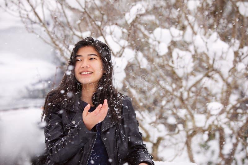 在穿黑皮夹克的降雪期间的青少年的女孩户外 库存图片