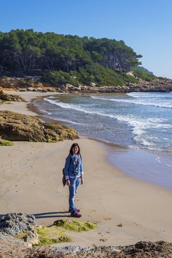 在站立在海滩的年轻女人佩带的便服的看法上,当看对照相机在一明亮的天时 库存图片