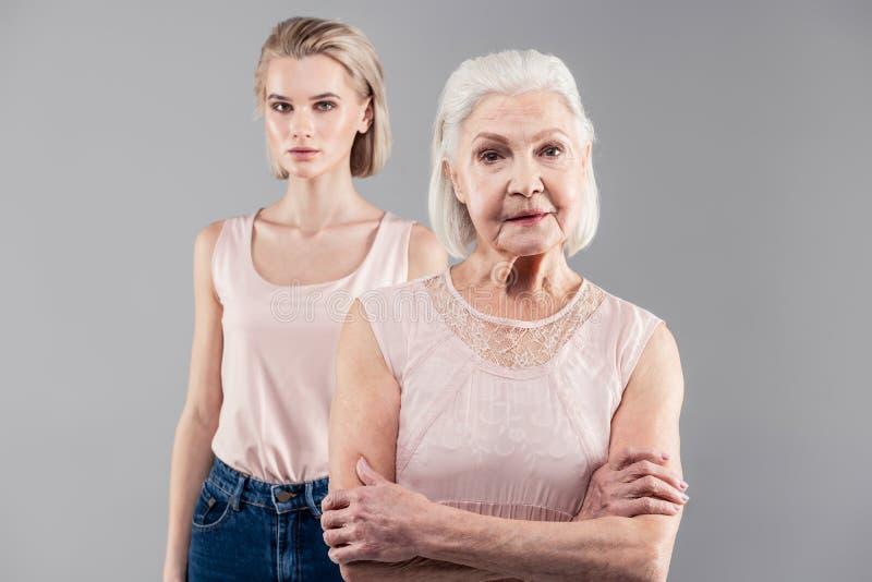 在第一个计划的珍贵的灰发的老妇人身分用横渡的手 免版税库存图片