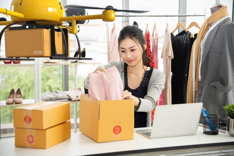 在箱子的年轻亚洲妇女粗麻布对顾客的交付的由空气寄生虫,与现代技术发货的小企业 免版税图库摄影