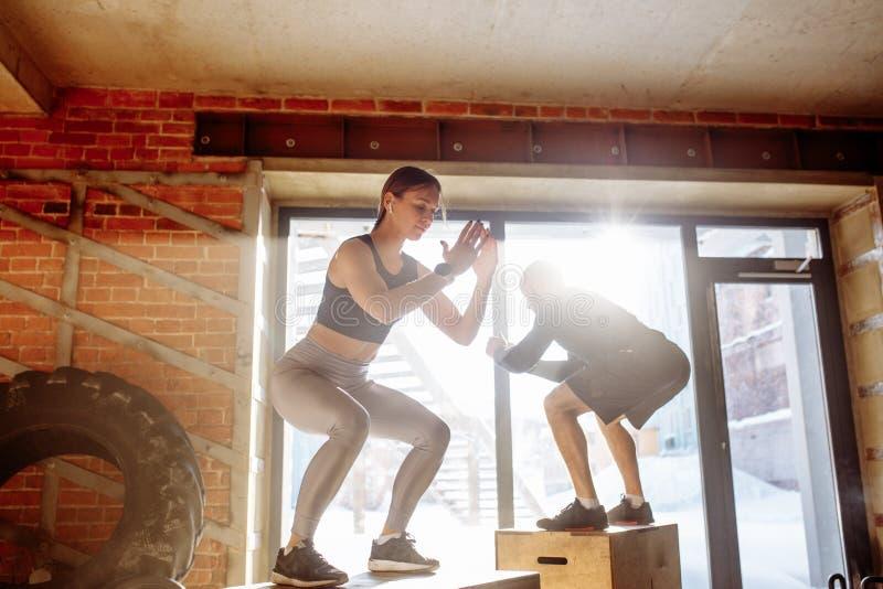 在箱子的男人和妇女跳跃的tohether在健身房,人的funcrional锻炼 免版税库存图片