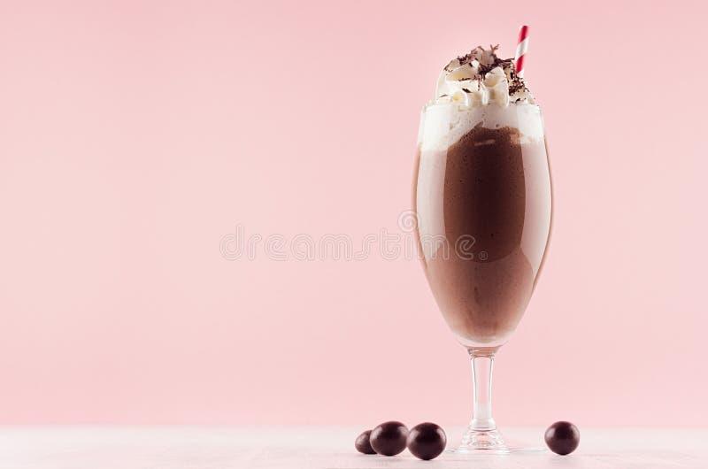 在精妙的葡萄酒杯装饰的糖果球的甜巧克力奶昔,打好的奶油,巧克力片,在轻的粉红彩笔的秸杆 免版税库存图片