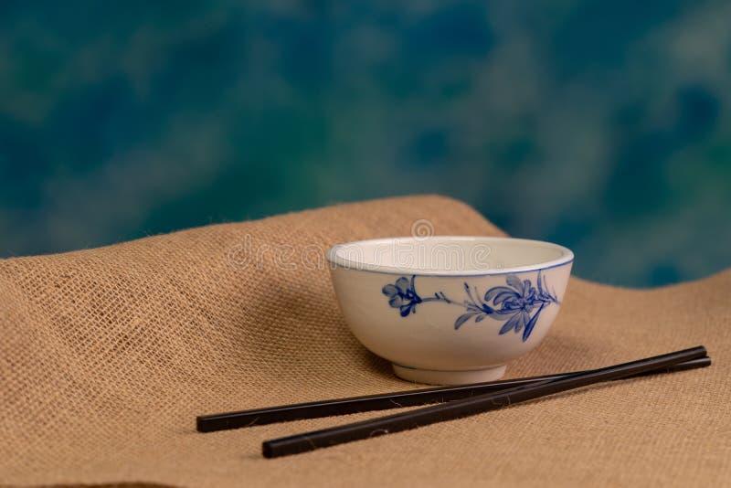 在粗麻布蓝色背景顶部的中国碗 免版税库存图片