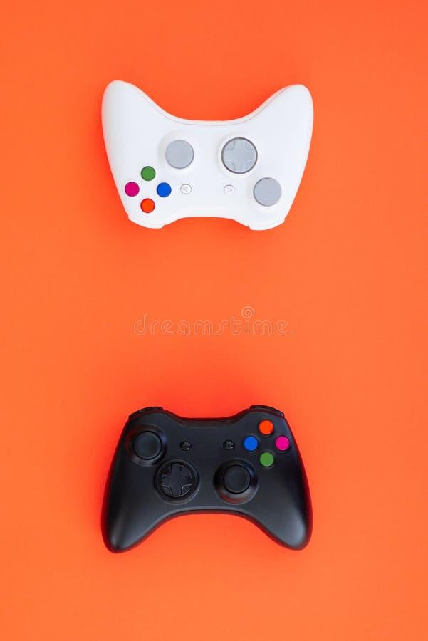 在红色背景的黑白控制杆 白色和黑gamepad在红色背景被隔绝 免版税库存图片