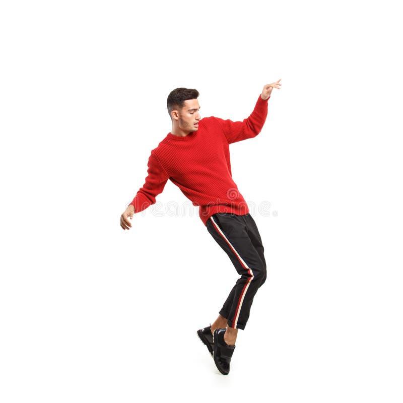 在红色高领衫和黑暗的裤子打扮的年轻时髦的人有条纹的在边舞蹈在白色背景 免版税库存图片
