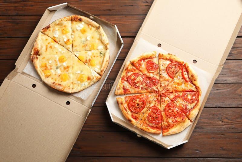 在纸板箱的热的奶酪披萨在桌,顶视图上 食物送货业务 库存图片