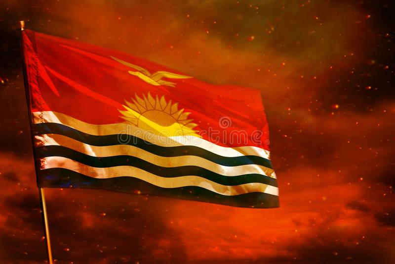 在绯红天空的振翼的基里巴斯旗子有烟柱子背景 麻烦概念 免版税库存照片
