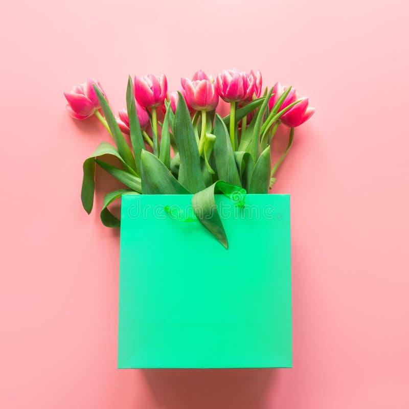 在绿皮书袋子的新鲜的红色郁金香花在桃红色 春天 免版税库存照片