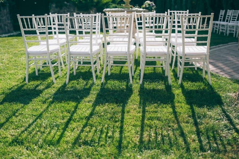 在绿草的白色椅子 图库摄影