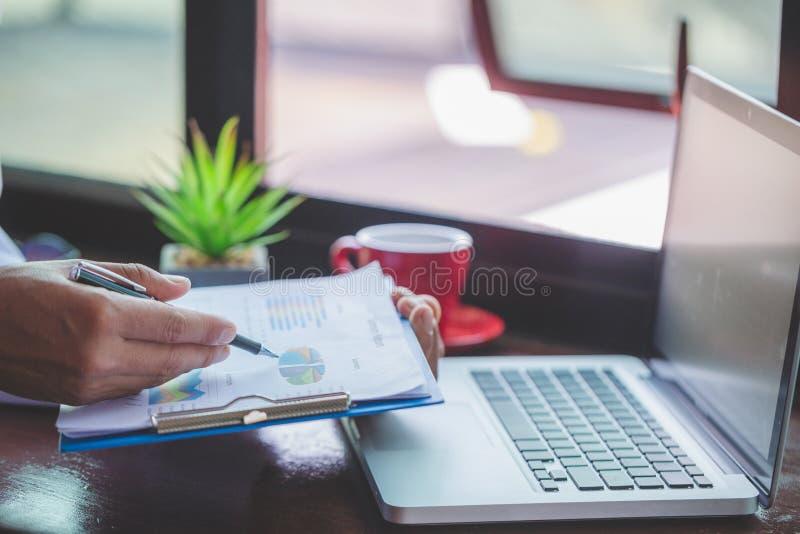 在统计和企业图表,拿着笔的商人的商人工作与图表文件,股票市场图一起使用 图库摄影