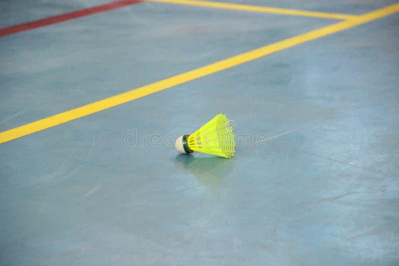 在羽毛球场边缘的一黄色shuttlecock 免版税库存照片