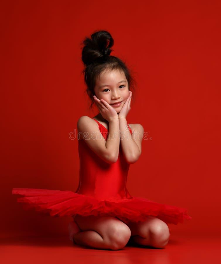 在美丽的礼服的逗人喜爱的女孩芭蕾舞女演员跳芭蕾舞者在红色跳舞 免版税库存图片