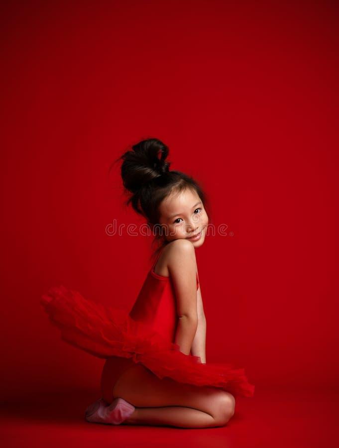 在美丽的礼服的逗人喜爱的女孩芭蕾舞女演员跳芭蕾舞者在红色跳舞 免版税库存照片