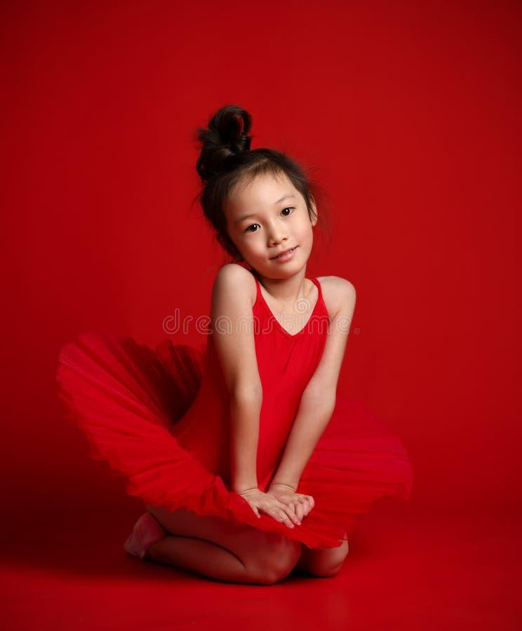在美丽的礼服的逗人喜爱的女孩芭蕾舞女演员跳芭蕾舞者在红色跳舞 免版税图库摄影
