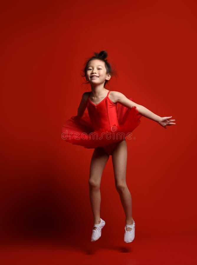 在美丽的礼服的逗人喜爱的女孩芭蕾舞女演员跳芭蕾舞者在红色跳舞 库存照片