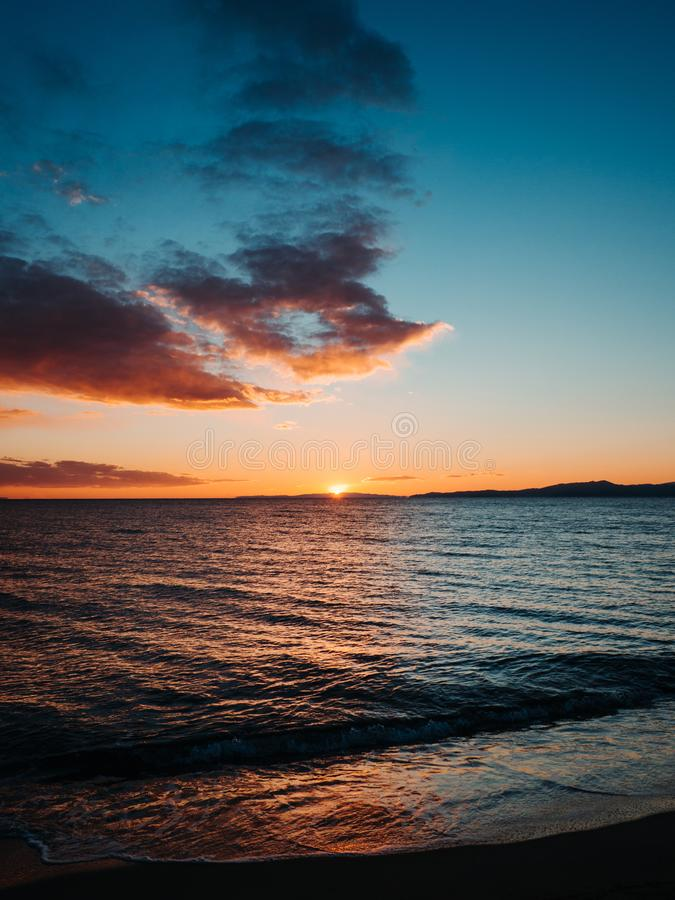在美丽的空的海滩-卡瓦拉,希腊的太阳设置 库存图片