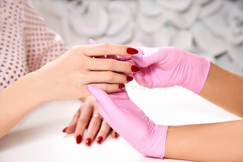 在美容院的修指甲 大师拿着client& x27;s手手特写镜头 桃红色手套,红色指甲油 免版税图库摄影