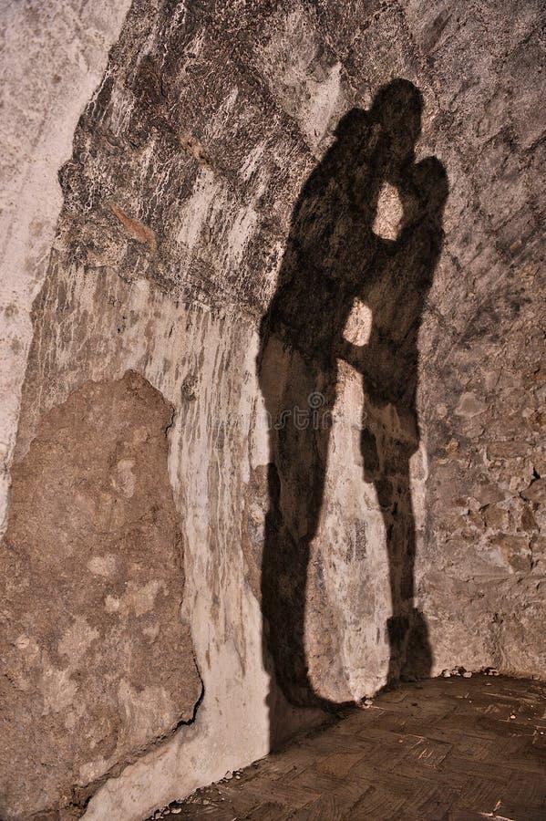 在石墙上的阴影夫妇亲吻 免版税库存照片