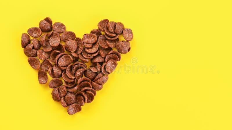 在看法下的上面,在心脏,文本的空间形状安排的黄色委员会的巧克力玉米片在右边 免版税图库摄影