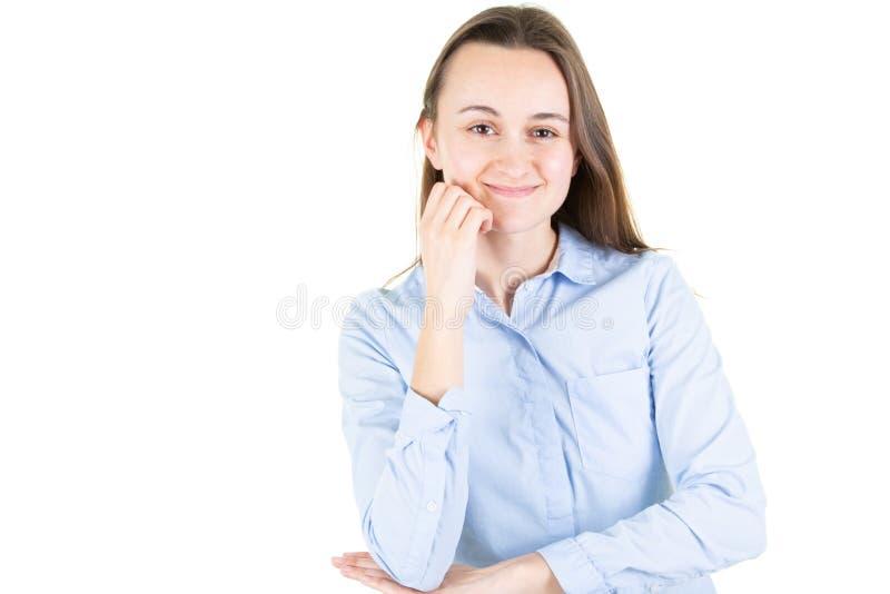 在看确信照相机的被隔绝的白色背景的美丽的年轻女人用在下巴想法的正面举的微笑手 免版税库存照片