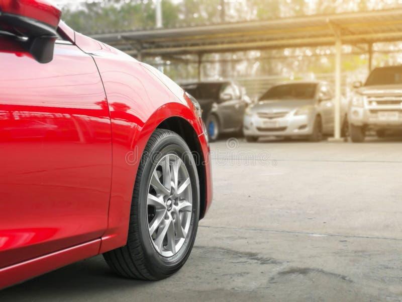 在的The新的红色汽车停放与在停车场的许多汽车 免版税库存图片