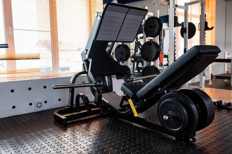 在现代健身房的空的腿新闻锻炼机器 库存照片