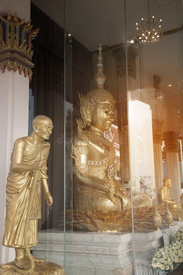 在玻璃的大古老金黄坐的菩萨展示在Wat Sangkas Ratanakhiri寺庙 免版税库存照片