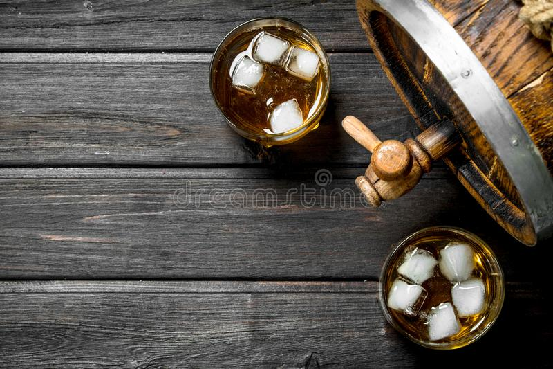 在玻璃的威士忌酒与冰和木桶 库存照片