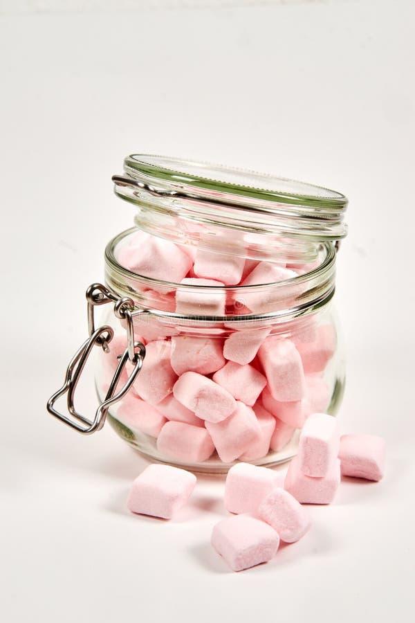 在玻璃瓶子的桃红色蛋白软糖,在白色背景 免版税库存照片