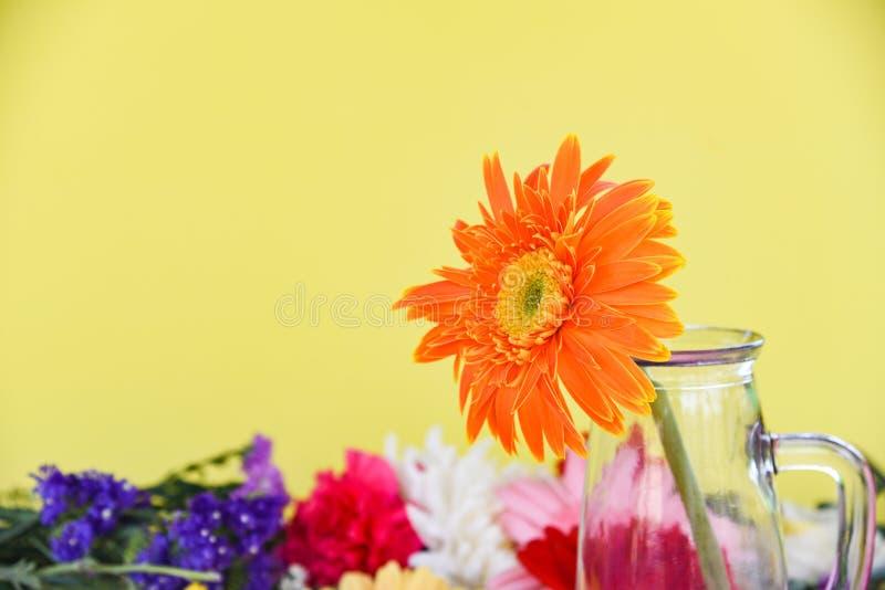 在玻璃瓶子的橙色大丁草雏菊花在五颜六色的花反弹夏天开花 免版税库存照片