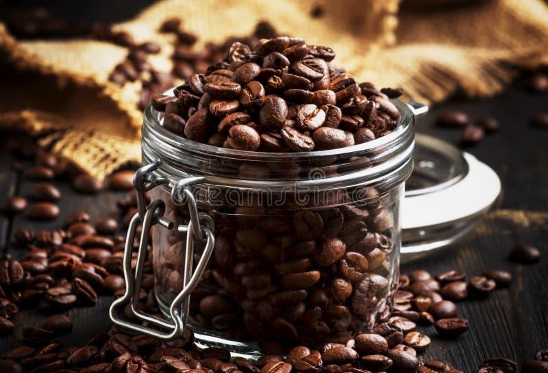 在玻璃瓶子,黑土气厨房用桌背景,选择聚焦的咖啡豆 库存照片
