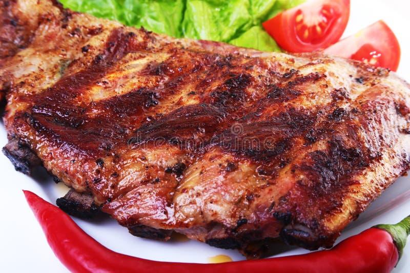 在烤肉和辣椒的排骨用蕃茄,莴苣在白色板材离开 免版税库存照片