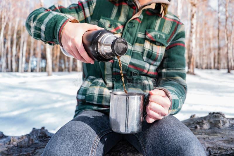 在热水瓶外面的倾吐的热的饮料在露营地 免版税库存图片