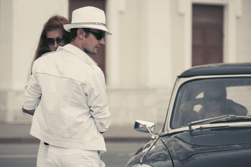 在爱的愉快的年轻时尚夫妇在葡萄酒汽车旁边 免版税库存照片