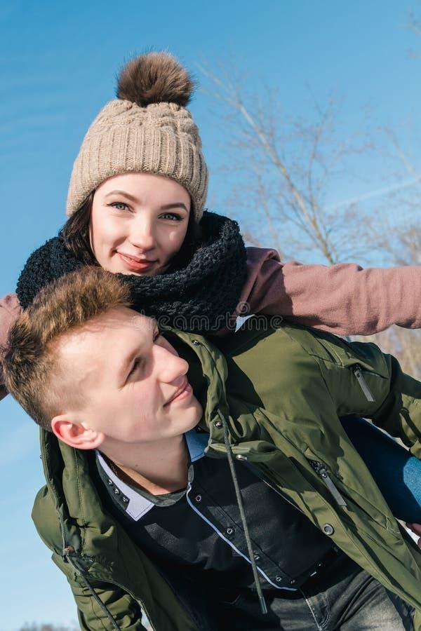 在爱的美好的年轻夫妇在公园在一个清楚的晴朗的冬日 女孩坐在她的男朋友和微笑背面 库存照片