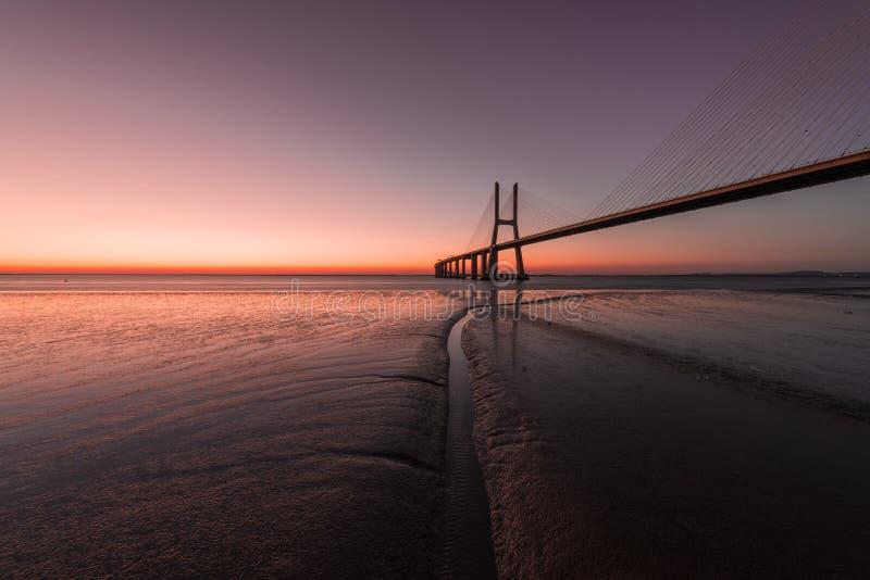 在瓦斯考de Gama Bridge的桃红色大气在里斯本 蓬特瓦斯考de Gama,里斯本,葡萄牙 免版税库存图片