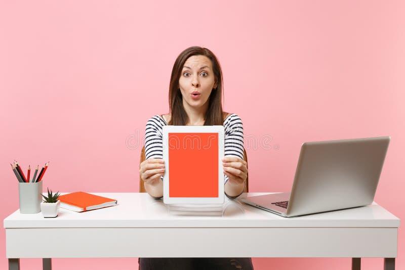 在照相机片剂计算机上的年轻惊奇的妇女陈列有空白的空的屏幕的坐工作在有当代的白色书桌 图库摄影